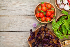 Fresh farmers tomatoes and basil. On wood table with copy space Royalty Free Stock Images