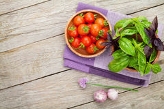 Fresh farmers tomatoes and basil. On wood table with copy space Stock Photo