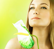 Fresh female face portrait. Beautiful model holding calla flower, perfect skin girl over green spring background, zen relaxing woman, spa and health care Royalty Free Stock Photography