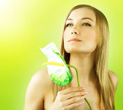 Fresh female face portrait. Beautiful model holding calla flower, perfect skin girl over green spring background, zen relaxing woman, spa and health care Royalty Free Stock Images