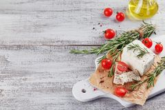 Fresh feta cheese with rosemary on white wooden serving board. Fresh feta cheese with cherry tomatoes and rosemary on white wooden serving board over light Royalty Free Stock Photos