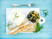 Fresh feta cheese with olives, basil, rosemary and bread slices. On white ceramic serving board over bright turquoise blue painted wooden background, top view Stock Photos