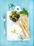 Fresh feta cheese with olives, basil, rosemary and bread slices on white ceramic serving board over bright turquoise Stock Photos