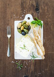 Fresh feta cheese with olives, basil, rosemary and bread slices on white ceramic serving board over rustic wooden Stock Images