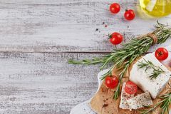 Fresh feta cheese with rosemary on white wooden serving board Royalty Free Stock Image