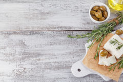 Fresh feta cheese with rosemary on white wooden serving board Royalty Free Stock Images