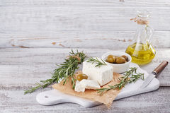 Fresh feta cheese with rosemary on white wooden serving board. Fresh feta cheese with green olives, olives oil and rosemary on white wooden serving board over Royalty Free Stock Photos