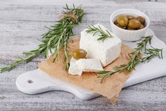 Fresh feta cheese with rosemary on white wooden serving board. Fresh feta cheese with green olives and rosemary on white wooden serving board over light wooden Royalty Free Stock Image