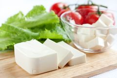 Fresh feta cheese and vegetables. Fresh cheese and vegetables on a wooden board Stock Image