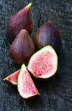 Fresh Figs. Whole and sliced, on weathered wood background Royalty Free Stock Image