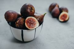 Fresh figs in bawl on gray background.  stock photo