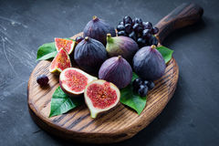 Fresh figs and black grapes on wooden board Stock Images