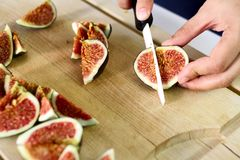 Fresh figs chops. Hand cutting fresh figs on wooden table Stock Photography