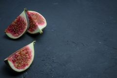 Fresh figs cut into slices. fig closeup on black concrete. place for text. diet fruit. royalty free stock image