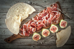 Fresh Figs With Ham. And flat bread on wood table, overhead shot Royalty Free Stock Image