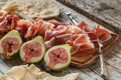 Fresh Figs And Ham. Fresh figs with ham on wood table Stock Images