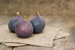 Fresh figs on hessian napkins on wooden background Royalty Free Stock Images