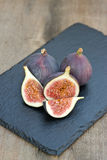 Fresh figs on hessian napkins on wooden background Royalty Free Stock Photos