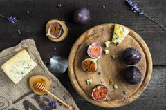 Fresh figs with honey and blue cheese on rustic wooden background. Overhead view stock photography
