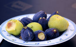 Fresh figs on a plate. Blue and green Stock Photos