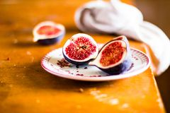 Fresh figs on a plate on a wooden table, selective focus. Autumn still life. Fresh fruits. Healthy and organic food royalty free stock image