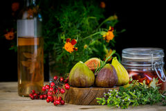 Fresh figs in wooden background with red berries and spice Stock Photos