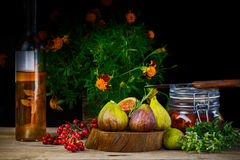Fresh figs in wooden background with red berries and spice Stock Image
