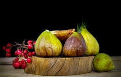 Fresh figs in wooden background with red berries Stock Photo
