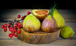 Fresh figs in wooden background with red berries Stock Photography