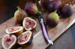 Fresh figs on wooden cutting board with knife. Royalty Free Stock Photo
