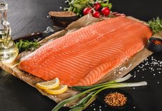 Fresh fillet salmon, red fish steak with spices and lemon on craft paper over dark stone background. Seafood, closeup. Fresh fillet salmon, red fish steak with royalty free stock photography