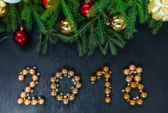 Fresh fir branch with Christmas toys. Beautiful background to insert text. View from the top. Christmas design wooden background. stock images