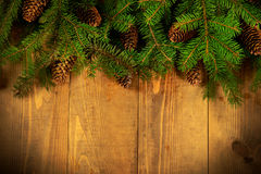 Fresh fir branches. Christmas Border - a strip of fresh fluffy fir branches with cones on a wooden background royalty free stock photography