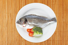 Fresh fish. With broccoli and cherry tomatoes in the white plate on on bamboo mat Stock Photography