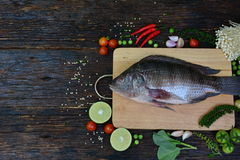 Fresh fish with aromatic herbs, spices, salt with lemon with cho Stock Photo
