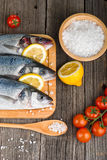 Fresh fish on chopping board with salt. Fresh fish on chopping board with lemon and vegetables on wooden table Royalty Free Stock Image