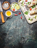 Fresh fish on cooking pan with ingredients, oil and spices on rustic background, top view. Healthy food Stock Photos