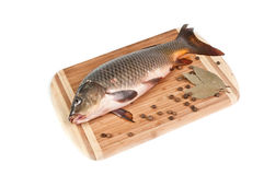 Fresh fish on the cutting board. With spices on white background Stock Photography