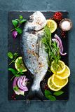 Fresh fish dorado. Raw dorado fish and ingredient for cooking on board. Sea bream or dorada fish on kitchen table. Top view stock photo