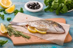 Fresh fish dorado. Spicy herb and vegetables healthy food spice on black stone board cooking. stock image
