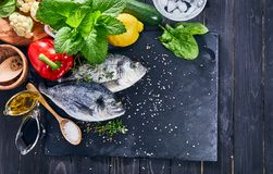 Fresh fish dorado top view. Spicy herb and vegetables. Spice on black stone board. Healthy food cooking. Royalty Free Stock Photography