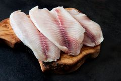 Fresh fish fillet on the chopping board on a black background. Organic fresh fish Royalty Free Stock Image