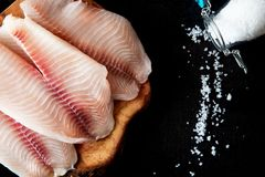Fresh fish fillet on the chopping board on a black background. Organic fresh fish Royalty Free Stock Photo