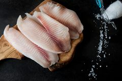 Fresh fish fillet on the chopping board on a black background. Organic fresh fish Royalty Free Stock Images