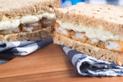Fresh fish finger sandwich on wholegrain in rustic kitchen setti Stock Photography
