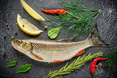 Fresh fish ide on a black stone slab surrounded by. Herbs, slices of lemon, peppers peas and salt. Selective focus. Top view Royalty Free Stock Photo
