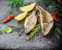 Fresh fish ide on a black stone slab surrounded by. Herbs, slices of lemon, peppers peas and salt. Selective focus. Top view Stock Photo