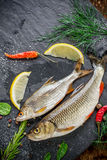 Fresh fish ide on a black stone slab surrounded by Stock Photo