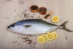 Fresh fish with lemon, parsley and spice on wooden cutting board isolated. On white Royalty Free Stock Photo