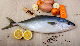 Fresh fish with lemon, parsley and spice on wooden cutting board isolated. On white Royalty Free Stock Image